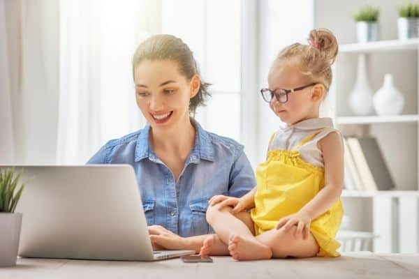 An organized mom sitting at a table using a laptop with preschool girl next to her