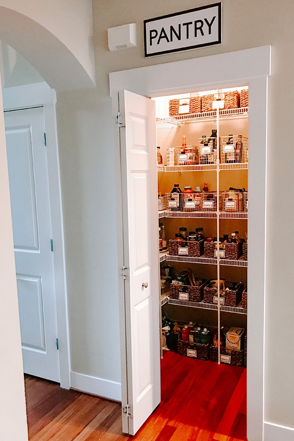 Pantry organized with baskets as seen from a distance. Pantry door open.
