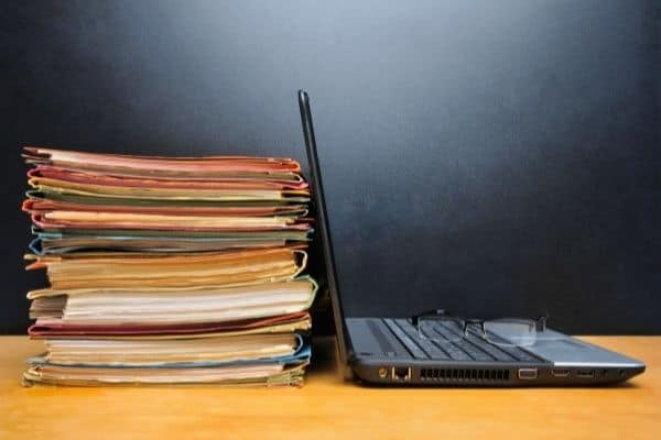 paper clutter solutions image of files full of paper and a laptop on desk