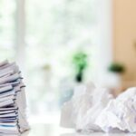 Crumpled papers and stack of documents in paper organization system