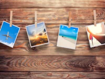 Colorful photographs pinned to clothesline with wood background