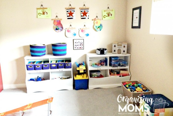 Playroom organization with white shelves filled with toys and artwork on walls