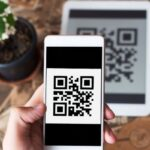 smartphone scanning qr code label on table with plant to side