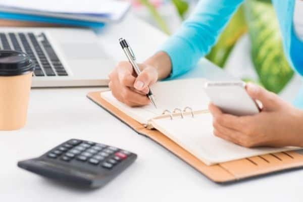 Woman doing quarterly planning with planner, cell phone and calculator at desk with computer.