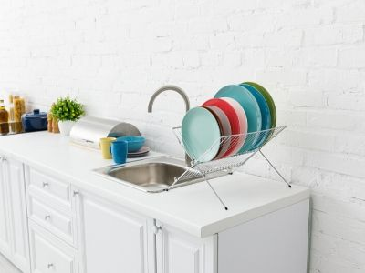 A white kitchen with colorful dishes drying next to sink.