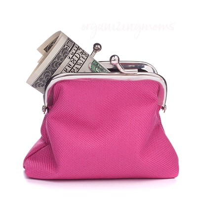 A close up of a pink coin purse with paper money inside.