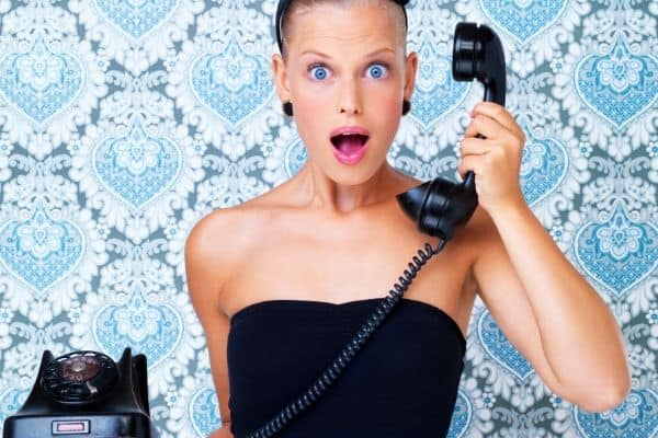 A woman answering telephone with surprised face