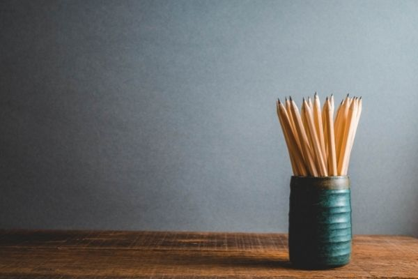sharpened pencils in pottery mug on desk in organized office