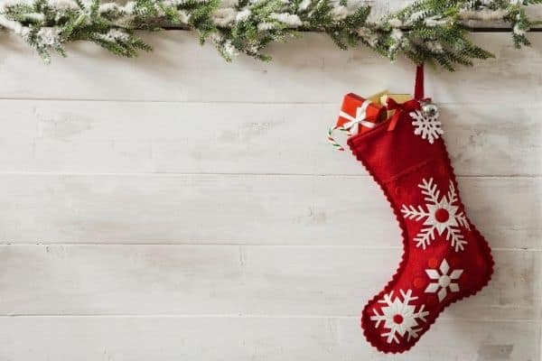 red stocking filled with small gift, garland above, on white background