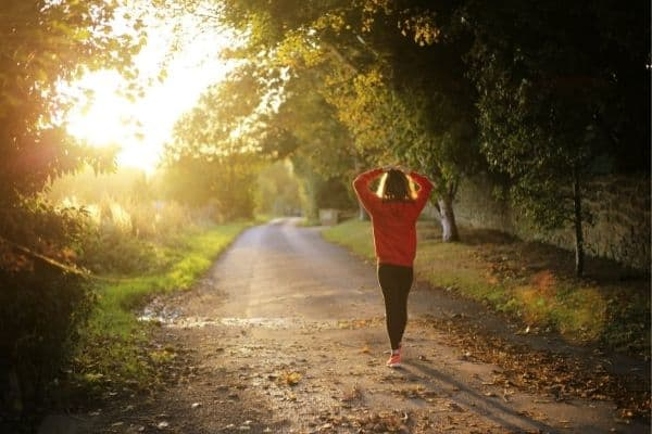 woman walking on dirt road with sun rising to symbolize how to get to 10000 steps a day