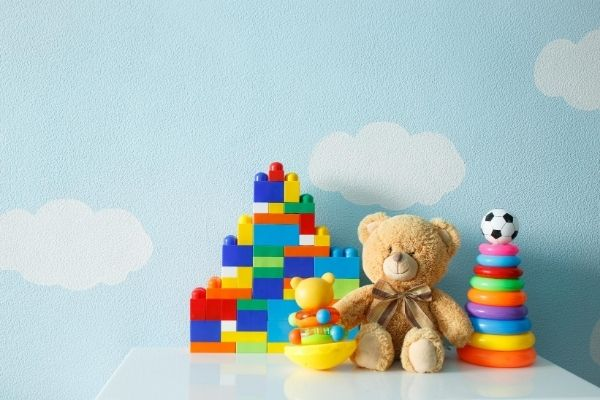 A teddy bear sitting on a table surrounded by toys