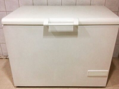 white deep freezer in front of wall with white tile