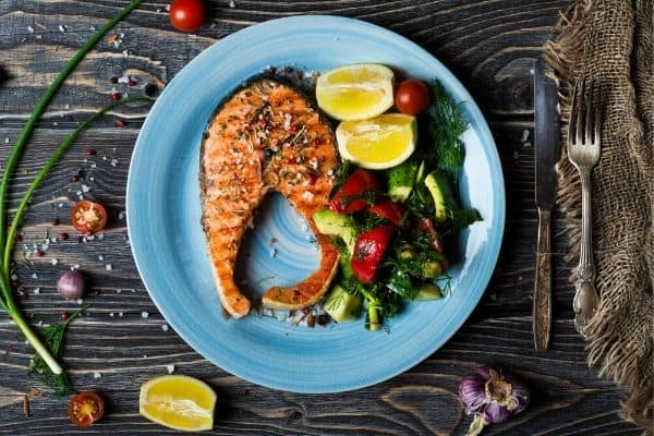 A blue plate of food on a table, with Salmon