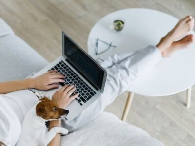 woman on laptop with dog sitting next to her, feet on white coffee table