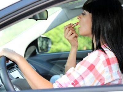 woman using beauty kit in car lipstick