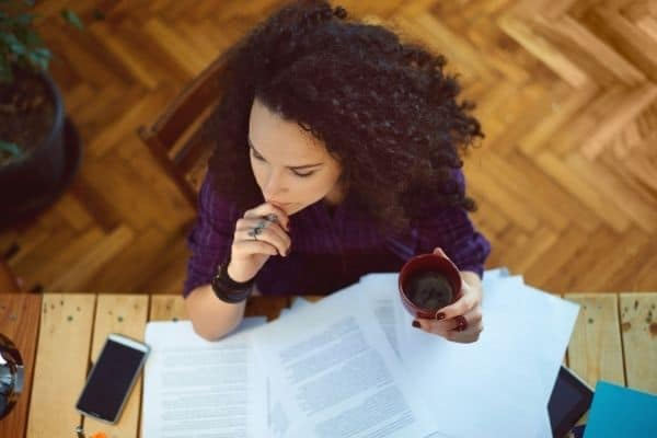 woman working at desk and drinking coffee